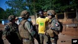 Des militaires français de l'opération Sangaris discutent avec un homme en civil dans une rue de Bangui, Centrafrique. 1er juin 2014