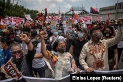 Anggota Kongres mengepalkan tangan mereka dan berbaris di sepanjang pengunjuk rasa di sepanjang Commonwealth Avenue, menjelang Pidato Kenegaraan tahunan terakhir Presiden Filipina Rodrigo Duterte, di Kota Quezon, Filipina, 26 Juli 2021. (Foto: REUTERS/Elo
