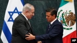 Mexico's President Enrique Pena Nieto, right, and Israeli Prime Minister Benjamin Netanyahu shake hands after a meeting at the Los Pinos presidential residence in Mexico City, Sept. 14, 2017.