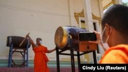 Seorang biksu memainkan beduk etelah Perdana Menteri Kamboja Hun Sen memerintahkan agar semua pagoda membunyikan lonceng dan genderang lima kali sehari sebagai pesan untuk melawan COVID-19, di Phnom Penh, Kamboja 24 Maret 2021. (Foto: REUTERS/Cindy Liu)