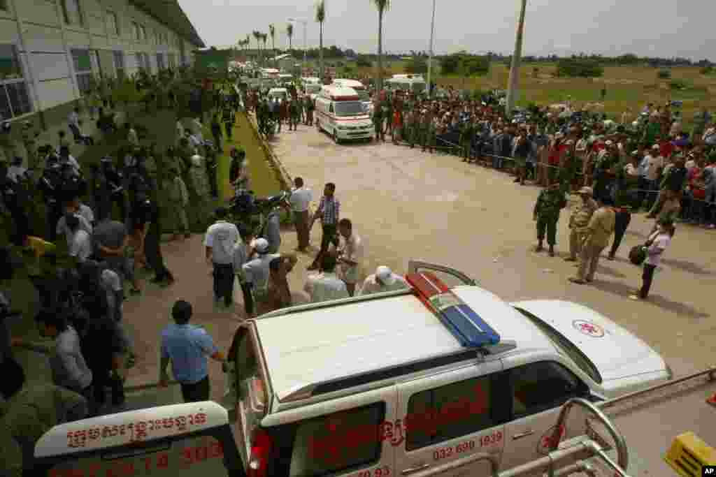 Ambulances park as they wait to transfer injured workers, at the site of a factory collapse in Cambodia, May 16, 2013.