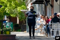 FILE - A member of the wait staff delivers food to outdoor diners along the sidewalk at the Mediterranean Deli restaurant in Chapel Hill, N.C., Apr. 16, 2021.