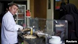 Syrian chef Wareef Hameedo prepares food for customers at Soryana restaurant in Gaza City, June 14, 2015.