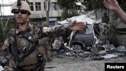 Para anggota pasukan Afghanistan berjaga-jaga di lokasi ledakan bom mobil di Kabul, Afghanistan (22/8). (Reuters/Ahmad Masood)