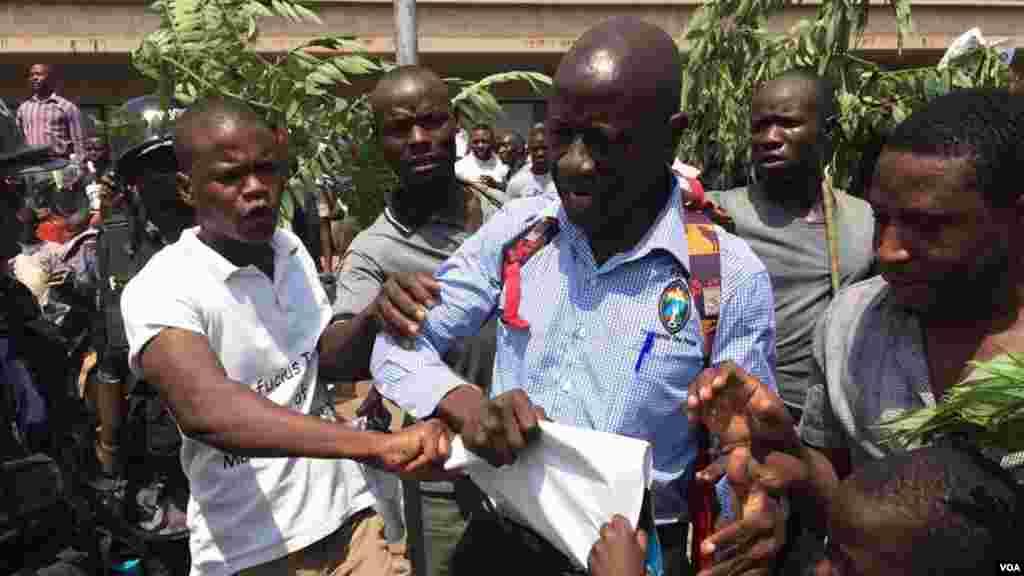Kizza Besigye a entouré de quelques-uns de ses partisans avant d'être arrêté par la police lors d'une manifestation à Kampala, Ouganda, février 2016.
