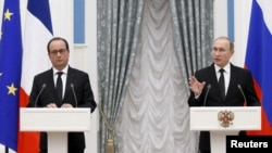 Russian President Vladimir Putin and French President Francois Hollande attend a news conference after meeting at the Kremlin in Moscow, Nov. 26, 2015.