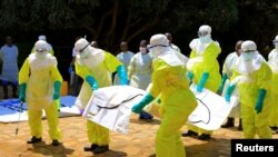 FILE - Congolese and World Health Organization officials wear protective suits as they participate in a training against the Ebola virus near the town of Beni in North Kivu province, Democratic Republic of the Congo, Aug. 11, 2018. Residents in the busy trading hub of Goma are also preparing to ward off the virus.