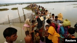 Rohingya refugees wait for boat to cross a canal after crossing the border through the Naf River in Teknaf, Bangladesh, Sept. 7, 2017.