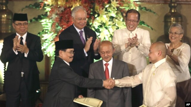 Government peace negotiator Marvic Leonen (R) and Moro Islamic Liberation Front chief negotiator Mohagher Iqbal (L) shake hands following a formal signing ceremony in Manila, Philippines, October 15, 2012.