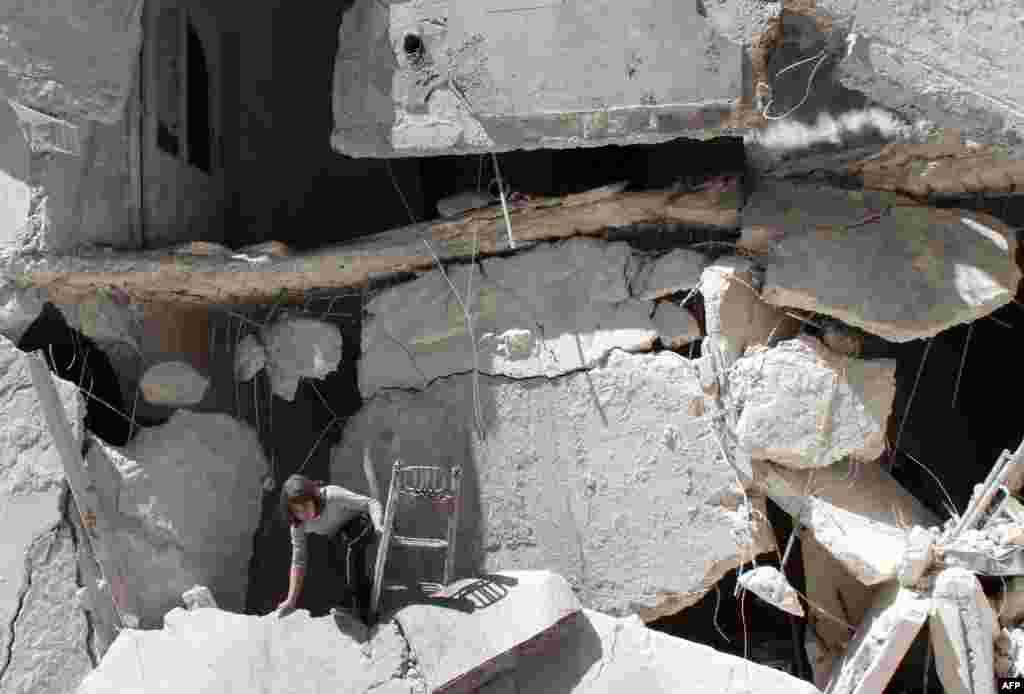 시리아 알레포 북부에 정부군의 공습이 있은 후한 소녀가 무너진 건물 사이로 소지품을 꺼내고 있다.