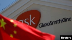 FILE - A Chinese national flag is seen in front of a GlaxoSmithKline office building in Shanghai.