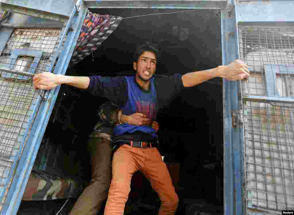 A supporter of Kashmiri lawmaker Sheikh Abdul Rashid, also known as Engineer Rashid, attempts to jump from a police vehicle after he was detained by Indian police during a protest in Srinagar, India. Dozens of supporters of Rashid were detained by police during a protest against the arrest of former Delhi University lecturer (SAR) Syed Abdul Rehman Geelani and also against the deaths of two youths in south Kashmir's Pulwama district, protesters said.