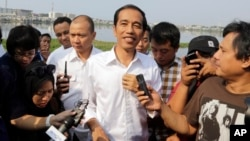 Indonesian presidential candidate Joko Widodo talks to the media during his visit at a reservoir development project in Jakarta, Indonesia, July 22, 2014.