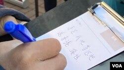 香港市民12月19日在大圍港鐵站外的街站寫聖誕卡給12港人,表示會等他們返回香港,希望他們堅持下去。(美國之音湯惠芸)