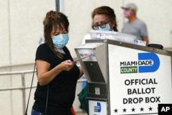 FILE - An election worker places a vote-by-mail ballot into an official ballot drop box outside a voting site in Miami, Fla.