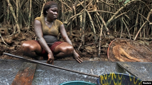 A woman coated in oil perches near a mangrove after fishing in a creek near the River Nun in Nigeria's oil state of Bayelsa, November 27, 2012.