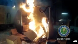 FILE - This file frame grab from video, provided by the Federal Aviation Administration (FAA) shows a test at the FAAs technical center in Atlantic City, N.J. last April, where a cargo container was packed with 5,000 rechargeable lithium-ion batteries. Officials say Jan. 27, 2016, a U.N. aviation panel is recommending a ban on shipping rechargeable batteries as cargo on passenger airliners because the batteries can create fires capable of destroying planes.