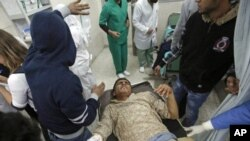 A wounded man is carried into the al-Jala hospital in Benghazi after an attack by Libyan military forces loyal to Muammar Gaddafi on a weapons dump near Benghazi in rebel-controlled eastern Libya killed 17 people.