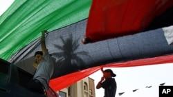 首都的黎波里居民在欧洲领导人的车队经过的街道上布置利比亚国旗以示欢迎