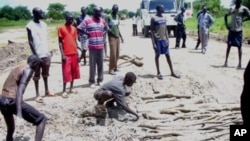 Trucks and passengers wait while local youths repair potholes on the Juba-Bor road in South Sudan