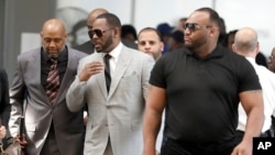 Musician R. Kelly, center, arrives at the Leighton Criminal Court building in Chicago for an arraignment on new sex-related felonies, June 6, 2019.