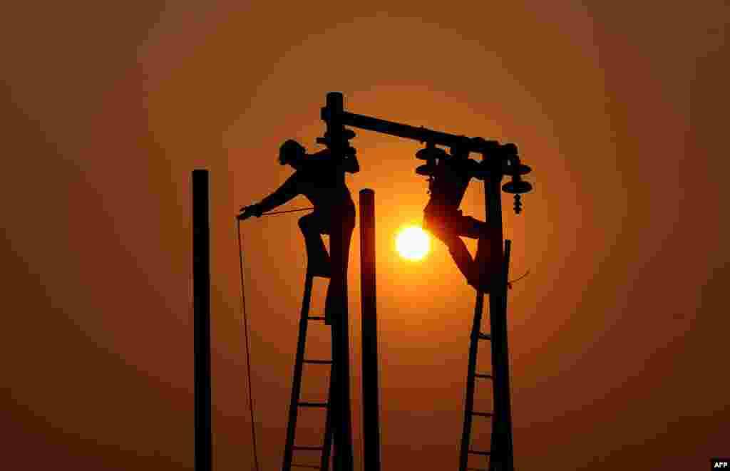 Indian electricians adjust electric cables set up temporarily on the banks of the river Ganga in preparation for the annual Hindu religious fair of Magh Mela in Allahabad.