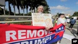 ທ່ານ Ray Bonachea ຢືນຖືປ້າຍທີ່ສະໜັບສະໜຸນໃຫ້ທຳການຟ້ອງຮ້ອງຕໍ່ປະທານາທິບໍດີທຣຳ ຢູ່ນອກສະຖານທີ່ຕາກອາກາດ Trump National Doral Miami ຂອງທ່ານທຣຳ ທີ່ມີສະໜາມກັອຟ ຢູ່ໃນນັ້ນ ຊຶ່ງຕັ້ງຢູ່ເມືອງ Dora, ລັດຟລໍຣິດາ ໃນວັນທີ 17 ທັນວາ, 2019