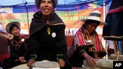 FILE - Aymara indigenous women grind grains of quinoa during a ceremony to celebrate the near completion of the International Year of Quinoa in Oruro, Bolivia, in 2013..