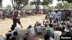 Warga Badaun, Uttar Pradesh, India utara berkumpul di lokasi di mana dua remaja perempuan korban perkosaan tewas dengan menggantung diri di pohon (28/5).