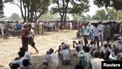 Onlookers sit at the site where two girls were hanged from a tree at Badaun district in the northern Indian state of Uttar Pradesh, May 28, 2014.