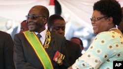 FILE: Zimbabwean President Robert Mugabe reacts with his deputy, Joice Mujuru, during Defence Forces Day in Harare, Tuesday, Aug. 14, 2012.