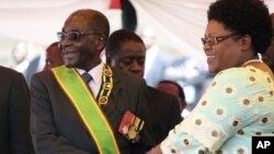 FLASHBACK: Zimbabwean President Robert Mugabe reacts with his deputy Joice Mujuru, during Defence Forces Day in Harare, Tuesday, Aug. 14, 2012.