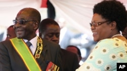 FILE: Zimbabwean President Robert Mugabe reacts with his deputy Joice Mujuru, during Defence Forces Day in Harare, Tuesday, Aug. 14, 2012.
