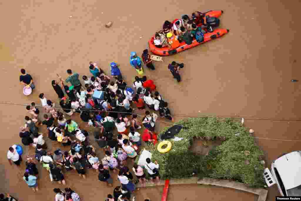 중국 허난성 정저우시의 수재민들이 홍수로 덮인 거리에서 구조대원을 기다리고 있다.