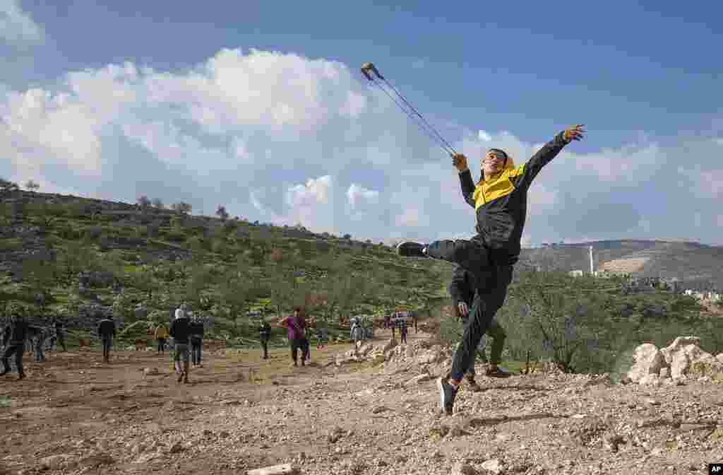 Palestinian protesters use slingshots against Israeli soldiers during clashes, at the outskirts of the West Bank village of Mughayer, north of Ramallah.