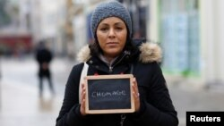"FILE - Malika Etchekopar-Etchart, unemployed, holds a blackboard with the word ""chomage"" (unemployment), the most important election issue for her, as she poses for Reuters in Chartres, France."