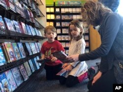 Elizabeth Gilless, of Memphis, Tenn., shows her children John, 3, and Ellen, 5, a movie from the children's section at the last Blockbuster on the planet in Bend, Ore., on Tuesday, March 12, 2019. (AP Photo/Gillian Flaccus)