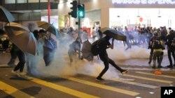 Seorang demonstran menendang kaleng gas air mata dalam bentrokan antara demonstran dengan polisi di Hong Kong, Minggu (10/11).