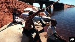 Des enfants font la pèche à côté d'un pont, sur le fleuve Limpopo, près de Xai Xai, Mozambique, 2 décembre 2000.