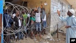 一名在利比里亞西點地區工作的國際救援組織人員向受隔離的利比里亞人拋投飲用水包。