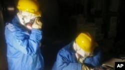 ຮູບພາບພວກພະນັກງານບໍລິສັດໄຟຟ້າໂຕກຽວ ເກັບຂໍ້ມູນໃນຫ້ອງ ຄວບຄຸມ ເຕົາແຍກນີວເຄລຍໜ່ວຍທີ 1 ແລະໜ່ວຍທີ 2 ທີ່ໂຮງໄຟຟ້າ Fukushima ວັນທີ 23 ມີນາ 2011.