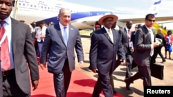 Israeli Prime Minister Benjamin Netanyahu (L) walks with Uganda's President Yoweri Museveni (R) after arriving to commemorate the 40th anniversary of Operation Entebbe at the Entebbe airport in Uganda, July 4, 2016.