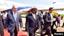 Thủ tướng Israel Benjamin Netanyahu (trái) đi cùng Tổng thống Uganda Yoweri Museveni (phải) sau khi đến để dự lễ kỷ niệm 40 năm Chiến dịch Entebbe tại sân bay Entebbe ở Uganda, ngày 4 tháng 7 năm 2016.