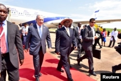 FILE - Israeli Prime Minister Benjamin Netanyahu (L) walks with Uganda's President Yoweri Museveni (R) after arriving to commemorate the 40th anniversary of Operation Entebbe at the Entebbe airport in Uganda, July 4, 2016.