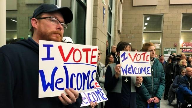 2019年12月9日,在北卡罗来纳州俾斯马克一个会议上,人们举着欢迎标语支持接收难民。 (美联社照片)