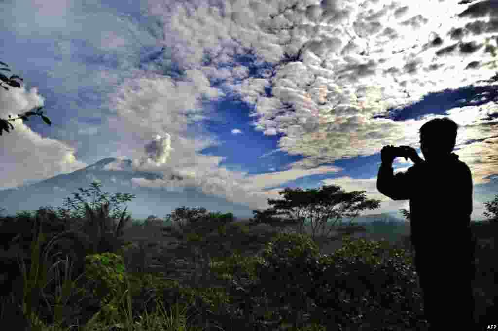 Seorang pria mengambil gambar saat gunung Agung mengepulkan asap di Kabupaten Karangasem, Bali.