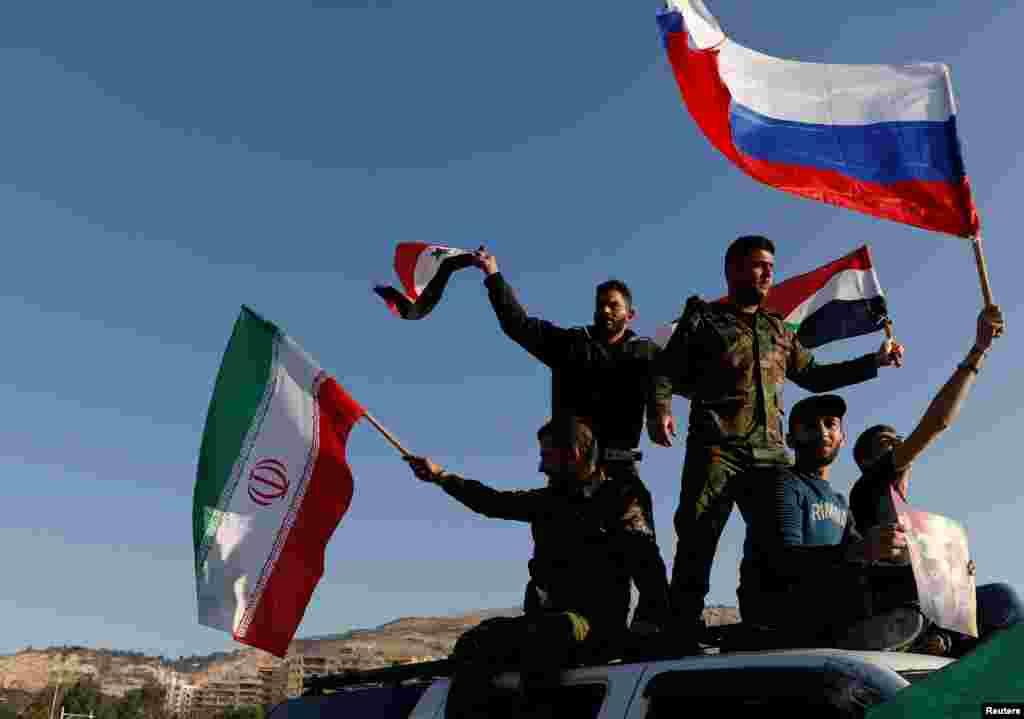 Sirios agitan banderas iraníes, rusas y sirias durante una protesta contra los ataques aéreos liderados por los EE. UU. en Damasco, Siria, el 14 de abril de 2018.