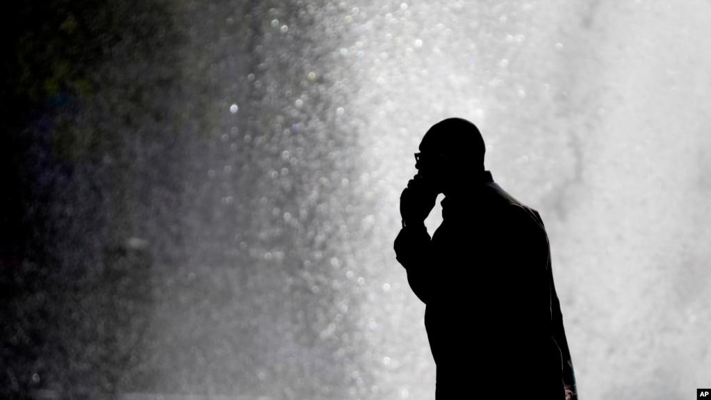 ARCHIVO- Un peatón habla por teléfono frente a una fuente en la ciudad de Philadelphia. 11-10-12.