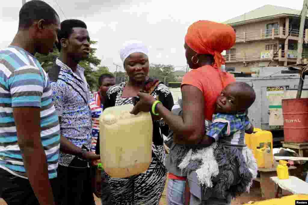 Uma mulher com um bebé às costas conversa sobre a falta de gasolina, explicando a necessidade de abastecer o gerador da sua casa em Abuja, Nigéria 25 de Maio 2015
