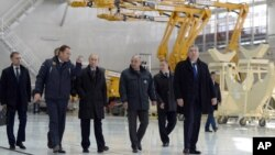 Russian President Vladimir Putin, third left, escorted by Russian Federal Space Agency head Igor Komarov, second left, walks through a working hall while visiting the Vostochny Cosmodrome near Uglegorsk, the city in eastern Siberia in the Amur region, Russia, October 14, 2015.